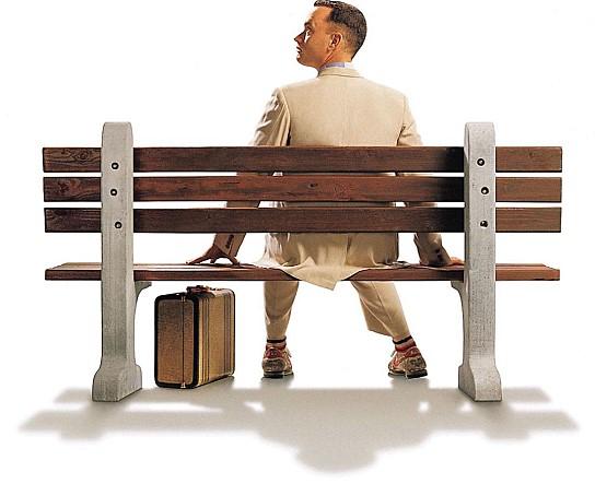 영화 <포레스트 검프>의 주인공 역 톰 행크스가 긴 의자에 앉아 있습니다.