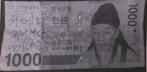 방문객이 욕설을 적고 던져놓은 실제 천 원짜리 지폐
