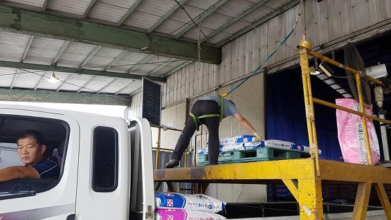 트럭에 배송을 나갈 사료를 싣고 있다.