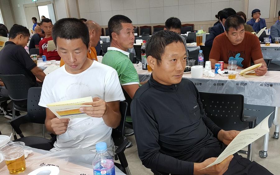 중국어로 된 출입국 행정 상식이 교육자료로 배포되고, 참가자들은  이 자료를 설명하는 '토크콘서트'를 경청하고 있다.