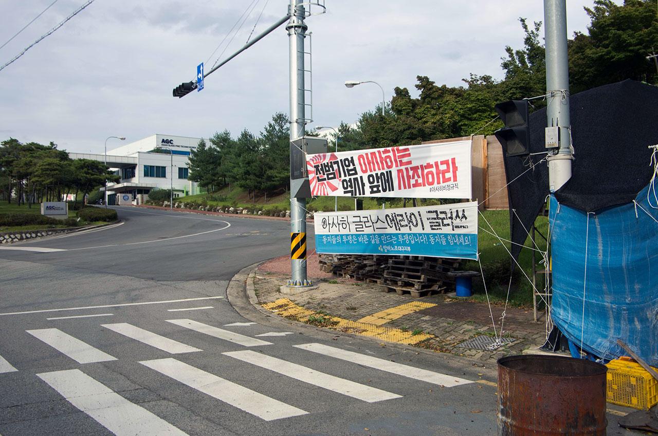 구미시 산동면 첨단기업로에 있는 원청회사 아사히글라스화인테크노코리아 정문 앞 농성장 옆에 '아사히글라스 에라이글르쓰'라 적힌 펼침막이 걸려 있다.