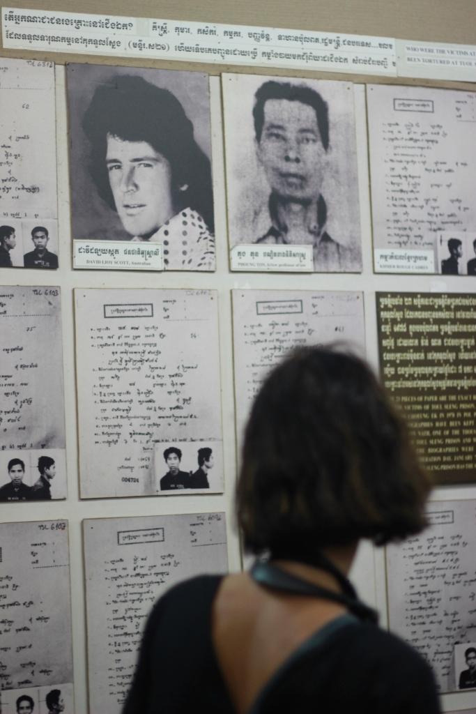 1970년대 내전 당시 크메르루즈 공산게릴라군에 의해 희생된 서양인의 흑백사진을 한 여행객이 지켜보고 있다.