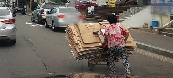 한 노인이 폐지 손수레를 끌면서 힘겹게 이동하고 있다(사진 속 등장인물은 기사 속 의뢰인과 관련이 없습니다).