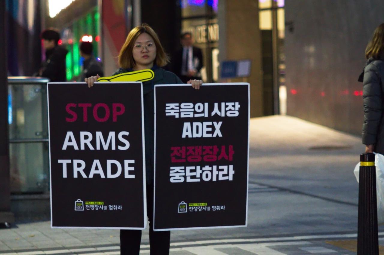 ADEX, 전쟁이 시작되는 곳 행사가 열린 호텔 앞에서 행사장으로 들어가는 사람과 차량을 향해 피켓을 들었다.