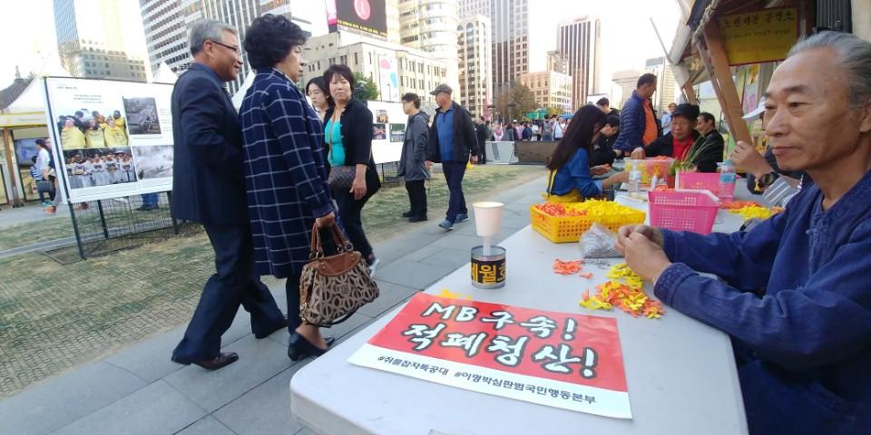 21일 서울 광화문광장에서 자원봉사자들이 세월호 리본을 묶고 있다.