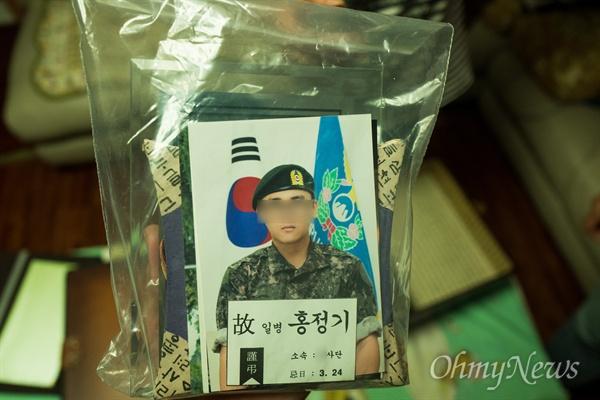 고 홍정기 일병의 군입대 사진과 유품이 비닐팩에 보관되어 있다.