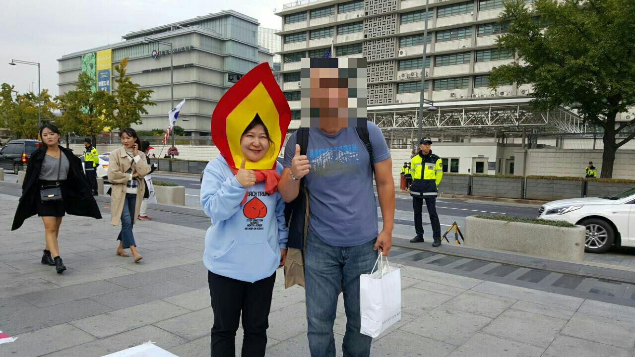 청년원정단 단원이 촛불 모양의 모자를 쓰고 광화문 앞을 지나는 외국인과 사진을 찍고있다.