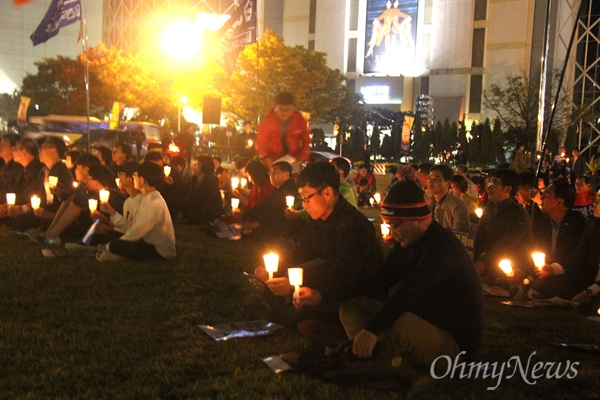 """'적폐청산과 민주사회건설 경남운동본부'가 28일 저녁 창원광장에서 연 """"촛불혁명 1년, 적폐청산과 사회대개혁 경남도민대회""""에 참석한 시민들이 촛불을 들고 있다."""