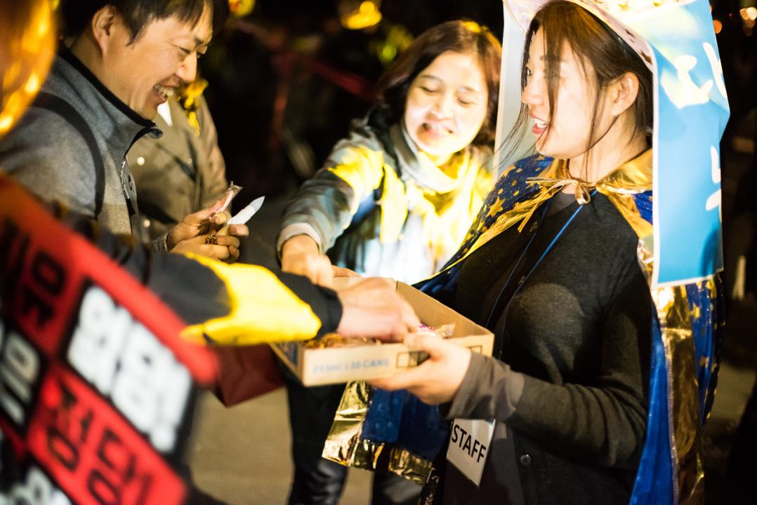 사탕을 나눠주는 촛불파티 스태프 한 촛불파티 스태프가 참가자들에게 사탕을 나눠주고 있다.