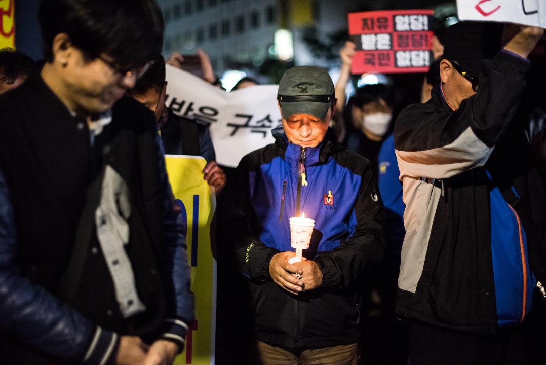 자유한국당 당사 앞에서 묵념하는 '촛불파티' 참가자들 '촛불파티' 참가자들이 자유한국당 당사 앞에서 묵념하고 있다.