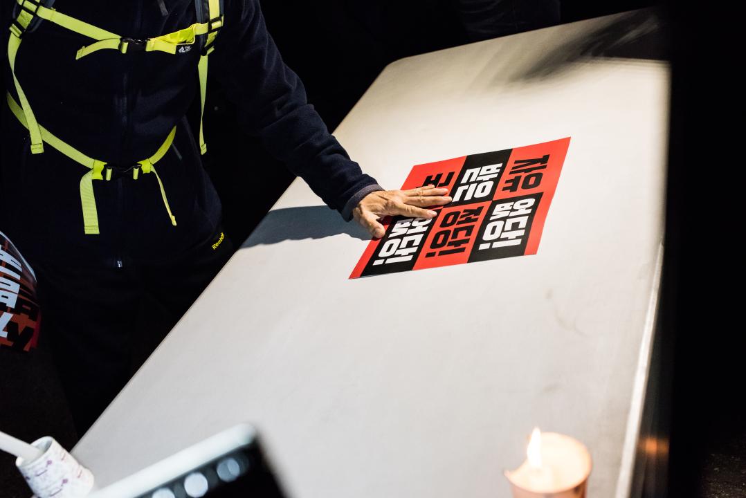 자유한국당 당사 앞에 피켓을 내려놓는 '촛불파티' 참가자 한 참가자가 자유한국당 당사 앞에 놓인 테이블에 피켓을 내려놓고 있다.