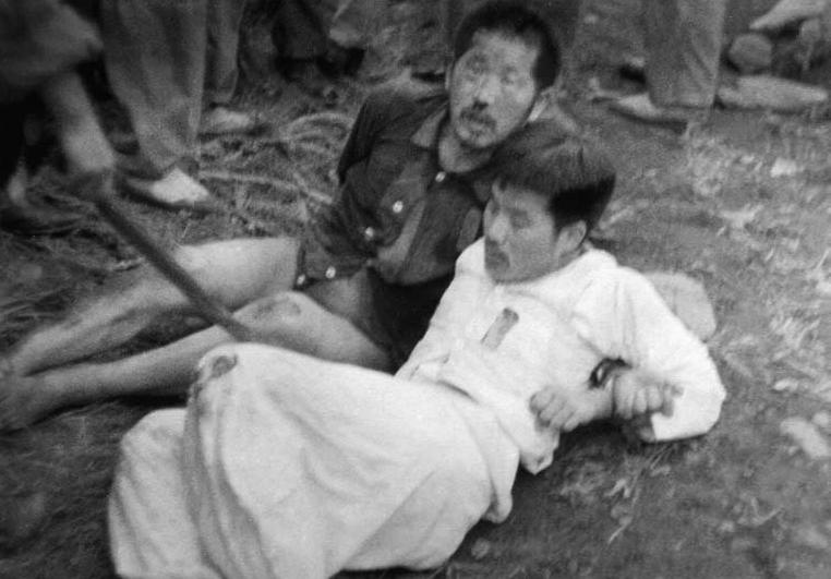 군경이 몽둥이로 저항하는 정치범들을 구타하고 있다.