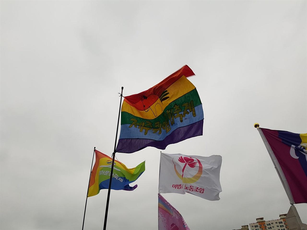 """제1회 '제주퀴어문화축제'의 공식 깃발 """"직접 손으로 그렸다""""던, 무지개 꼬리가 달린 말 마스코트가 그려진 주최측 깃발이 제주의 세찬 바닷바람에 휘날렸다. 흐린 날씨에도 나를 포함한 참가자들은 무척 즐거웠다."""