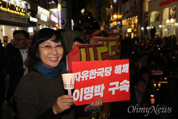 4일 오후 대구백화점 앞에서 열린 '촛불 1년'을 기념하는 집회에서 한 시민이 촛불과 '자유한국당 해체, 이명박 구속'이라고 쓴 피켓을 들고 있다.