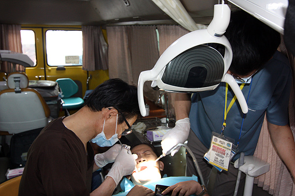 """""""아! 아파라!"""" 정형태 원장에게 처음으로 치과진료를 받는 아주머니가 아파서 얼굴을 찡그리고 있다."""