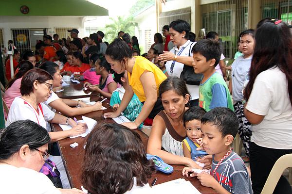 필리핀 자원봉사자들이 환자들을 분류하고 번호표를 나눠주고 있다