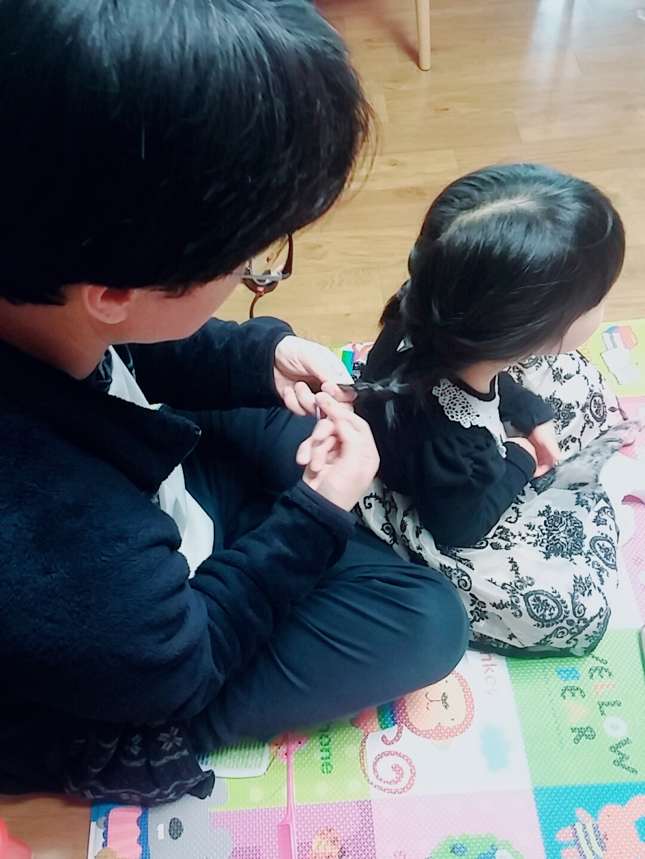 딸의 머리를 땋고 있는 남편.