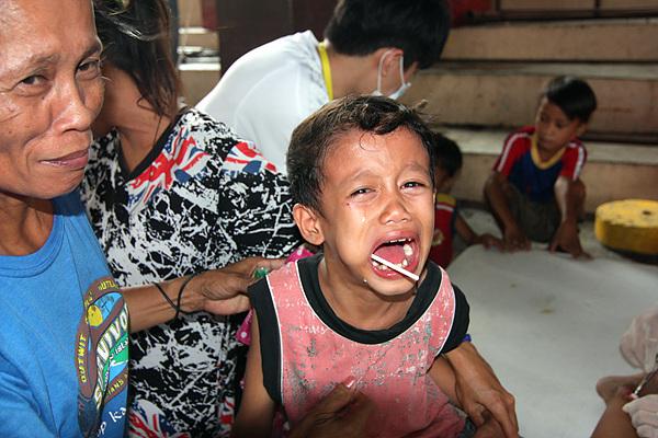의사가 무서운 아이가 소아과 진료를 받은 후 울고 있다. 손주를 달래며 웃는 할머니 모습. 소아과 진료를 담당하는 의사들은 진료가 끝난 아이에게 사탕을 주며 달래야 했다