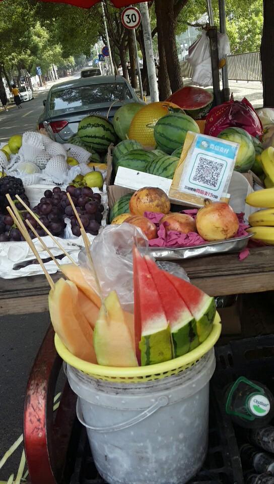 거리에서 과일을 파는 포장마차에서도 모바일 결제가 가능하도록 QR코드를 제공하는 모습