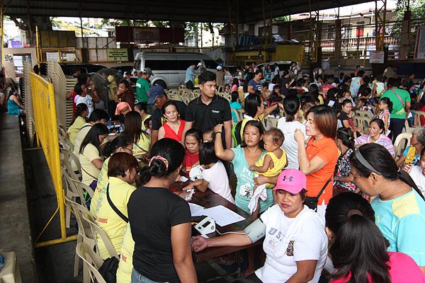 필리핀 자원봉사자들이 환자를 분류하고 번호표를 나눠주고 있다