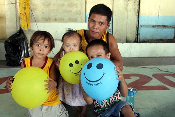 세명의 어린아이를 데리고 진료받으러 온 필리핀 현지인이 선물 받은 풍선을 들고 기념촬영했다