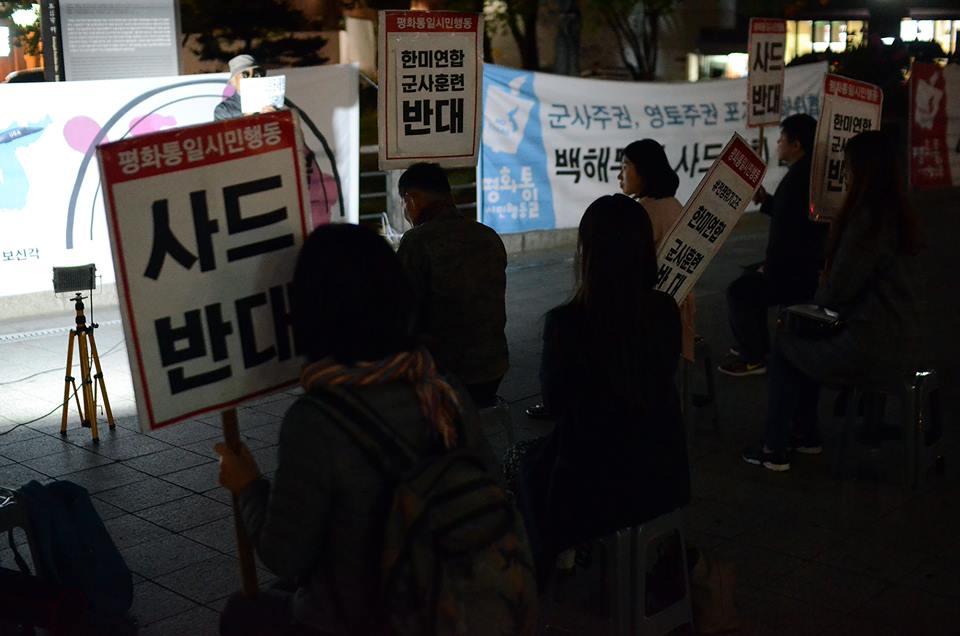'사드반대', '전쟁위기 고조 한미연합군사훈련 반대' 피켓을 들고 있는 회원들