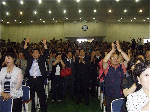 """2007년 7월 4일 열린 이명박 예비후보 정책설명회에서 울산상공회의소 7층 대강당을 가득 메운 참석자들이 이명박 예비후보가 """"의혹에 대해 """"믿어주시겠습니까""""고 외치자 이명박을 연호하고 있다"""