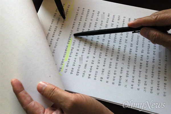 여운환 아름다운컨벤션 대표가 지난 10월 25일 광주의 한 호텔에서 <오마이뉴스>와 만나 인터뷰를 하는 도중, '일본 야쿠자 의식 참석설'을 반박하기 위한 판결문을 내보이고 있다.