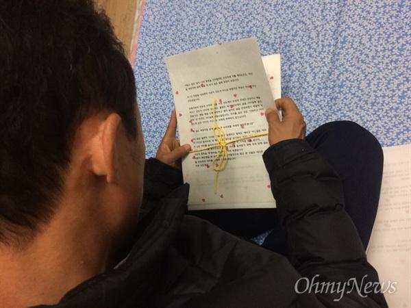 세월호 미수습자. 단원고 2학년 남현철 학생의 아버지 경원씨가 17일 저녁 목포신항에서 아들의 관에 넣을 일기를 살펴보고 있다. 경원씨는 2014년 4월 16일 참사 이후 일기를 쓰면서 하루 하루를 버텼다.