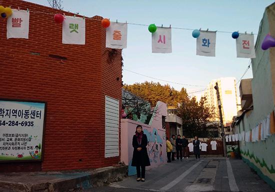 포항양학지역아동센터(센터장 정해자) 주변 골목에서는 지난 11월 20일부터 <빨랫줄 시화전>이 열리고 있다. 아이들이 쓰고 그린 시와 그림을 천에 프린트한 작품들을 담벼락과 전봇대 사이에 매단 빨랫줄에 걸어서 전시했다. 이 전시회는 한국예술인복지재단 파견예술인 사업의 일환으로 진행된 것으로, 예술인 3명이 그 동안 6개월째 아이들의 시쓰기, 그림 그리기, 사진 찍기 지도를 해왔다. 사진은 포항양학지역아동센터 골목 입구 허공에 걸린 <빨랫줄 시화전> 안내 문구와 풍선, 옆집 벽에 걸린 작품들의 모습이다.