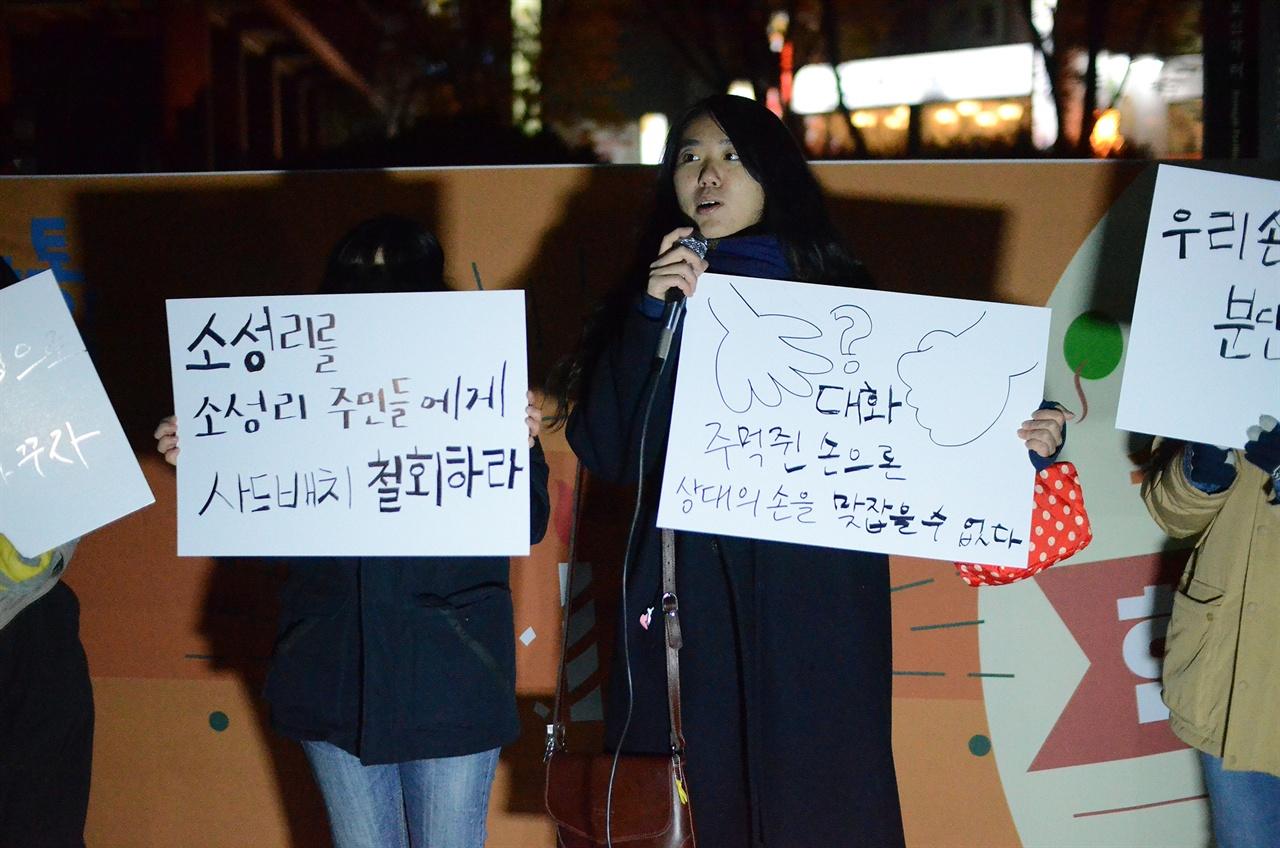 수요평화촛불 참가자가 '주먹 쥔 손으로 상대의 손을 맞잡을 수 없다'란 구호를 적은 피켓을 들고 있다.