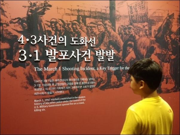 제주 4·3평화공원에 전시된 '4·3사건의 도화선, 3·1발포 사건 발발' 설명을 읽고 있는 어린이.