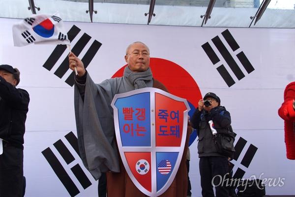 '빨갱이는 죽여도 돼'라고 쓴 방패 모형을 든 성호스님이 26일 오후 대구백화점 앞에서 열린 집회에서 태극기를 흔들고 있다.