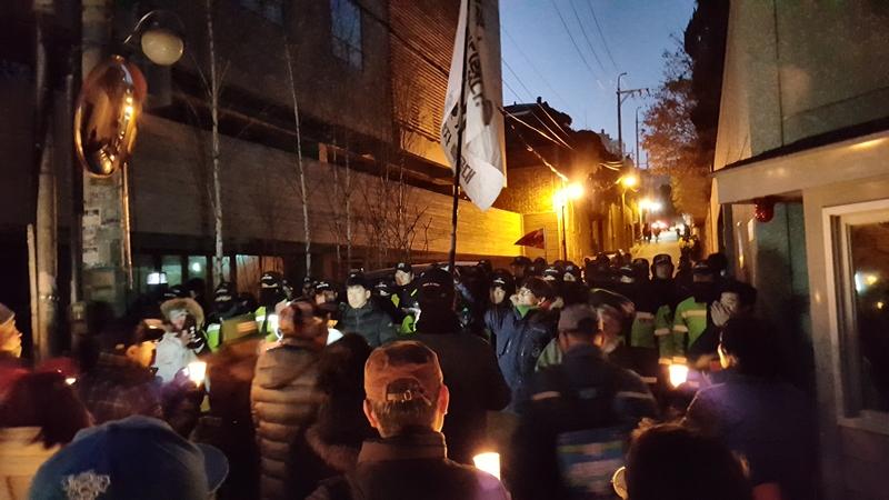 16일 오후 서울 강남구 학동역 인근에서 열린 '명박산성 허물기 촛불난장 문화제'에 참석한 사람들과 경찰이 이명박 전 대통령 자택 앞에서 마주 서 있다.