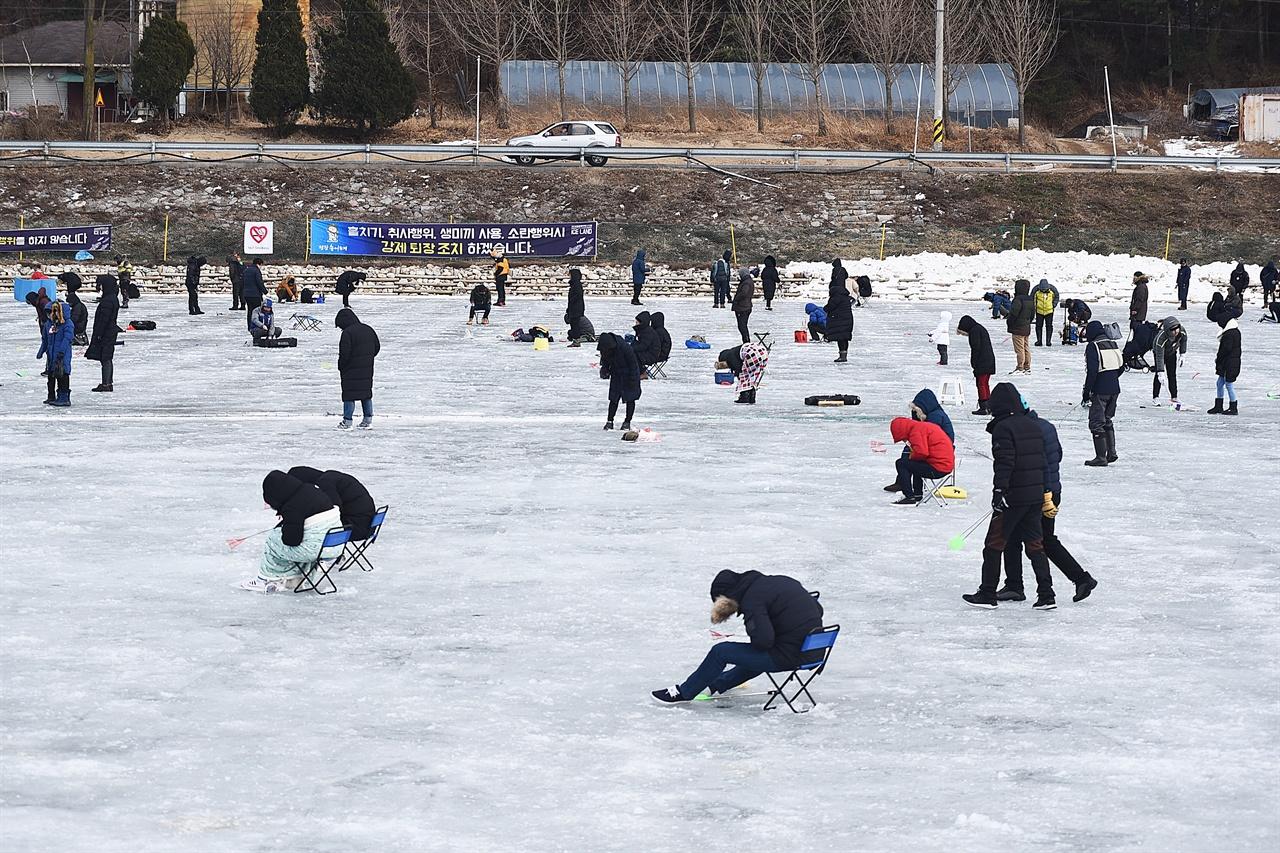 평창 송어축제 얼음낚시터  추운 날씨에도 불구하고 얼음 구멍에 낚시를 넣고 송어를 낚고자 하는 사람들