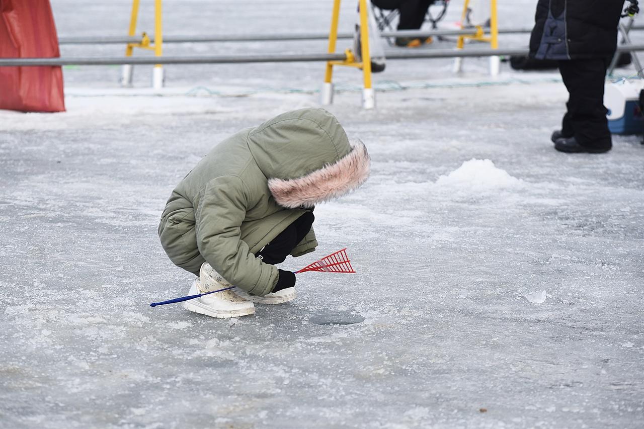 송어낚시터의 동심  송어를 잡고자 얼음 구멍을 응시하는 꼬마