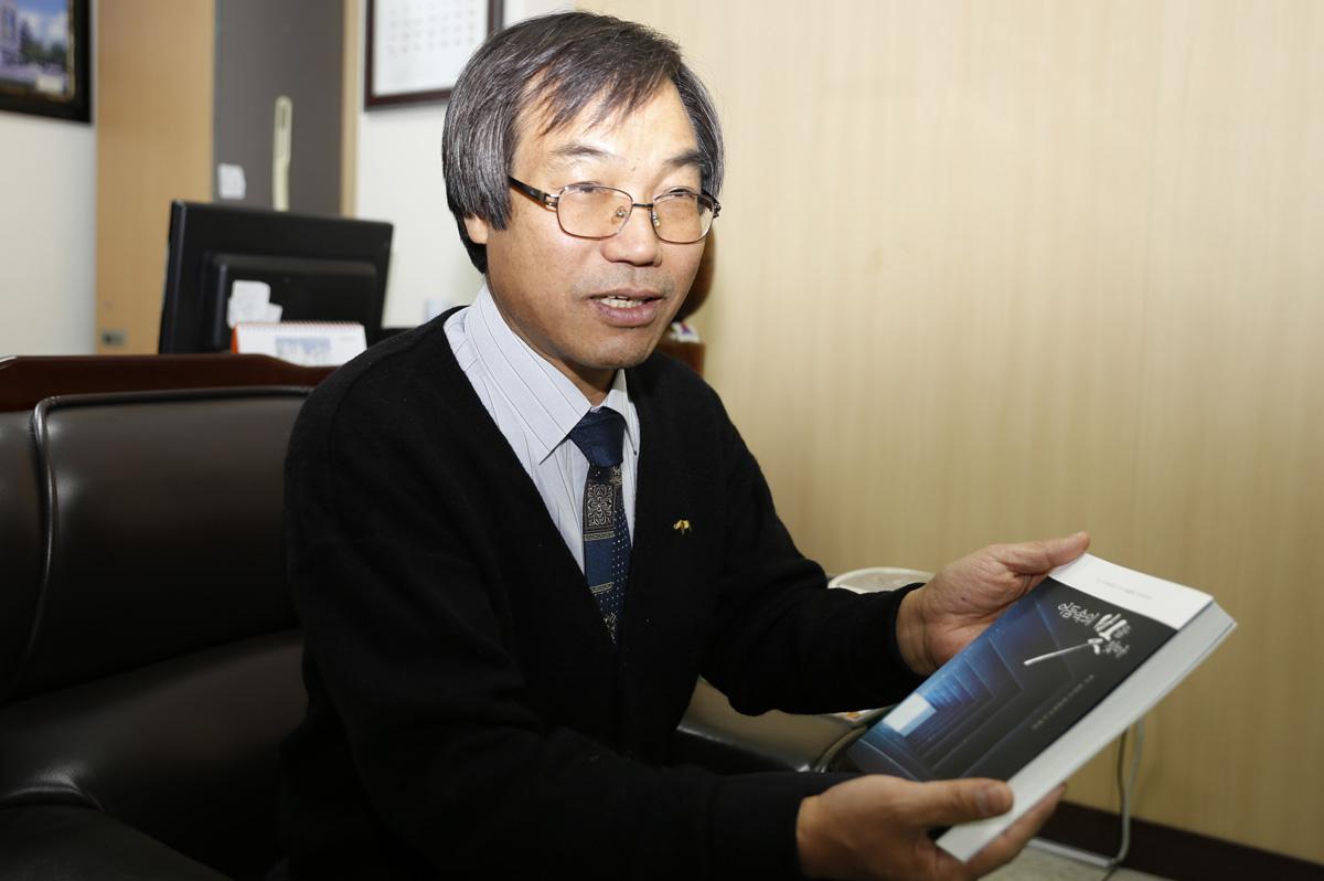 김갑주 회장이 최근 펴낸 자전에세이 <어둠속의 빛을 찾아>를 들어보이고 있다. 김 회장은 이 책으로 얻은 수익금 전액을 '어둠속의 빛 체험관' 건립부지 마련 비용으로 내놓았다.