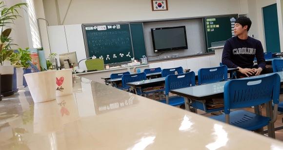 운동장 쪽 창가에서 찍은 교실 앞쪽 사진. 낮아진 여닫이 칠판 속에 텔레비전이 보인다.