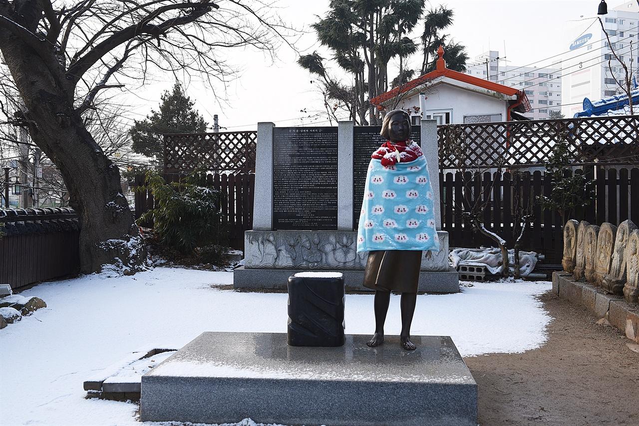 군산 평화의 소녀상 눈 내린 겨울 아침, 동국사 서쪽편에 당당하게 서 있는 소녀상. 뒤에 참사비가 있다