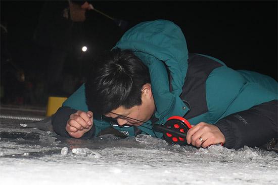 밤 낚시 중인 관광객 개막 첫 날인 6일과 7일 야간에는 산천어 밤낚시 장에는 많은 관광객들이 몰려 얼음 구멍속을 들여다 보며 낚시에 열중하고 있다.