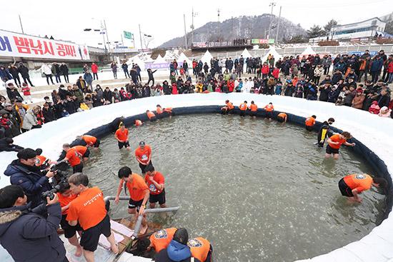 산천어 체험장 2018화천산천어축제장 산천어맨손잡기 체험장에서 참가자들이 물속에서 산천어를 잡기위해 들여다 보고 있다.