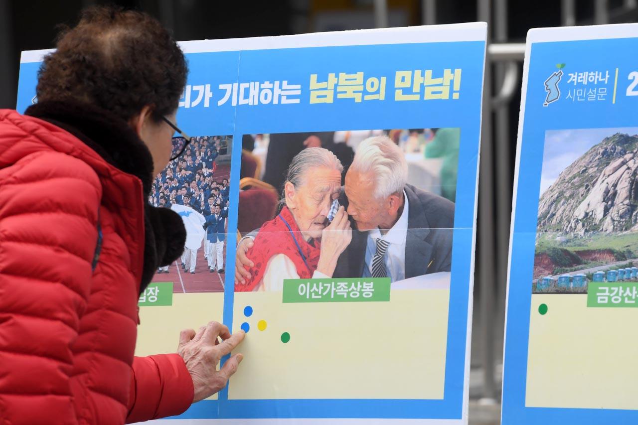 우리겨레하나되기운동본부 회원들이 8일 오후 서울 종로구 세종문화회관 앞에서 '남북대화 환영과 평창올림픽 성공 개최를 위한 서울시민 캠페인'을 펼치고 있는 가운데 '2018 우리가 기대하는 남북의 만남'중 '이산가족상봉'에 한표를 붙이고 있다. 2018.01.08