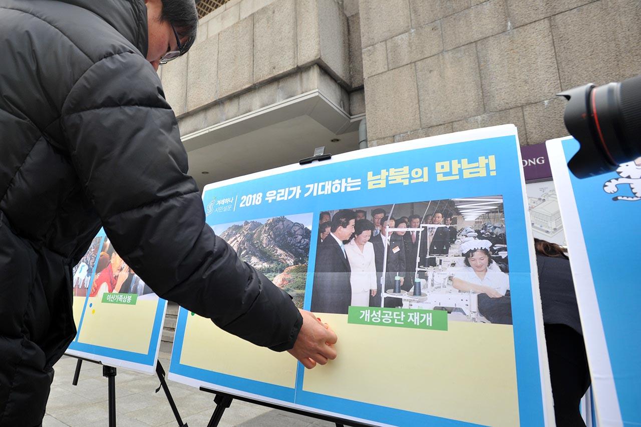우리겨레하나되기운동본부 회원들이 8일 오후 서울 종로구 세종문화회관 앞에서 '남북대화 환영과 평창올림픽 성공 개최를 위한 서울시민 캠페인'을 펼치고 있는 가운데 한 시민이 '2018 우리가 기대하는 남북의 만남'중 개성공단 재개'에 한표를 붙이고 있다. 2018.01.08
