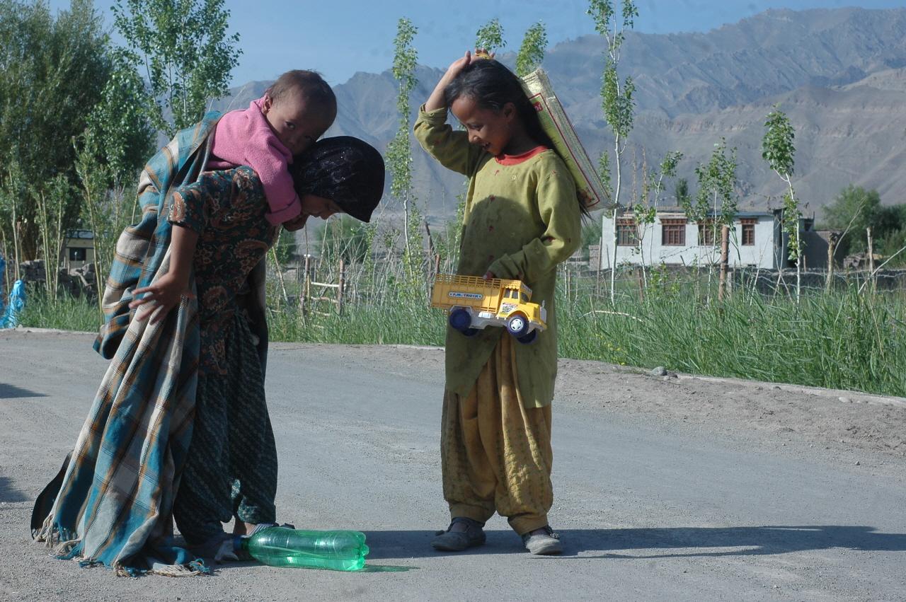 길거리에서 칭얼거리는 남동생을 업어주고 있는 네팔 아이