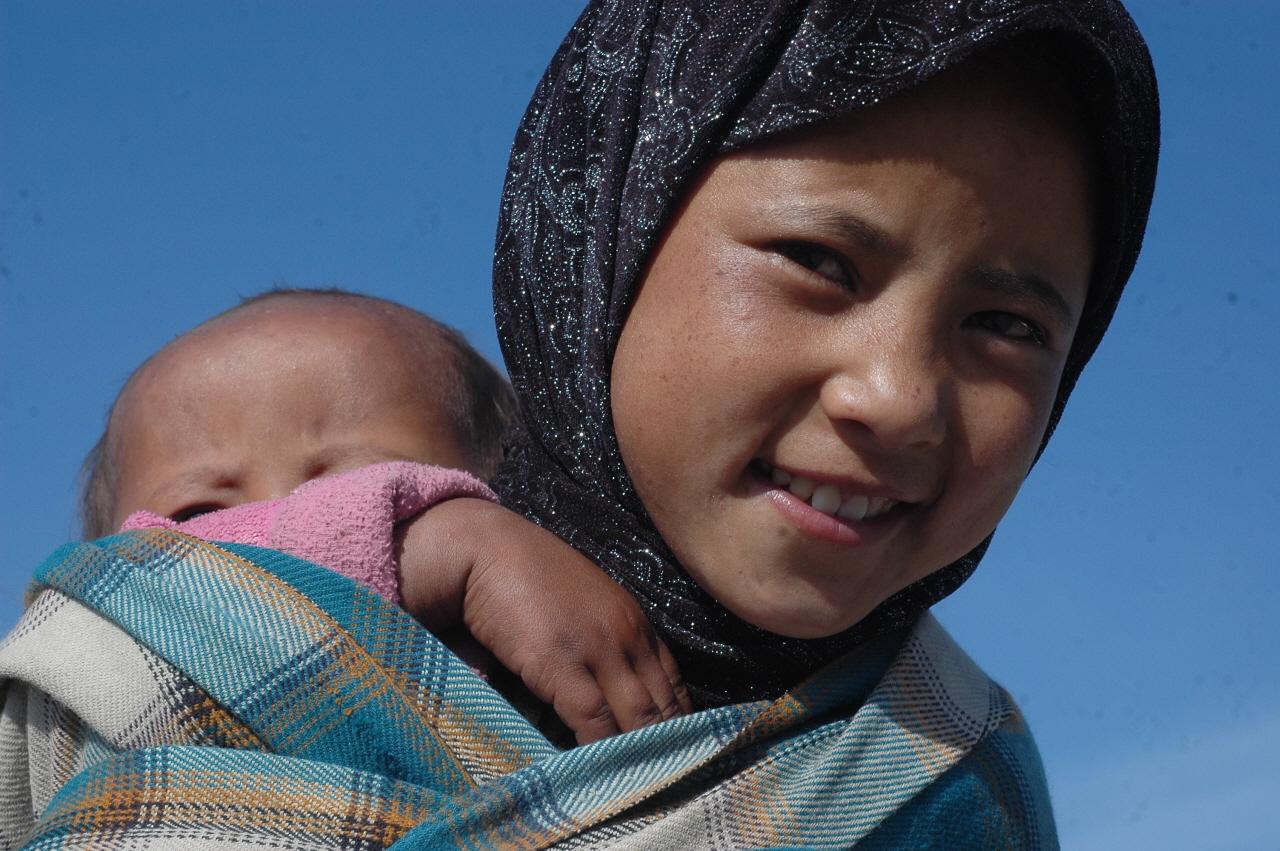 동생을 업고 슬픈 눈빛으로 웃고 있는 네팔 소녀