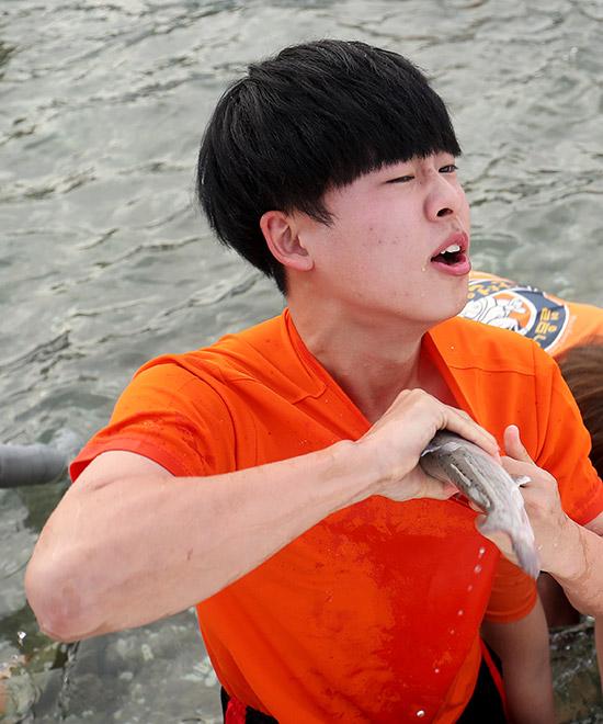 산천어 맨손잡기 체험 참가자가 손으로 잡은 산천어를 옷 속에 넣고 있다.