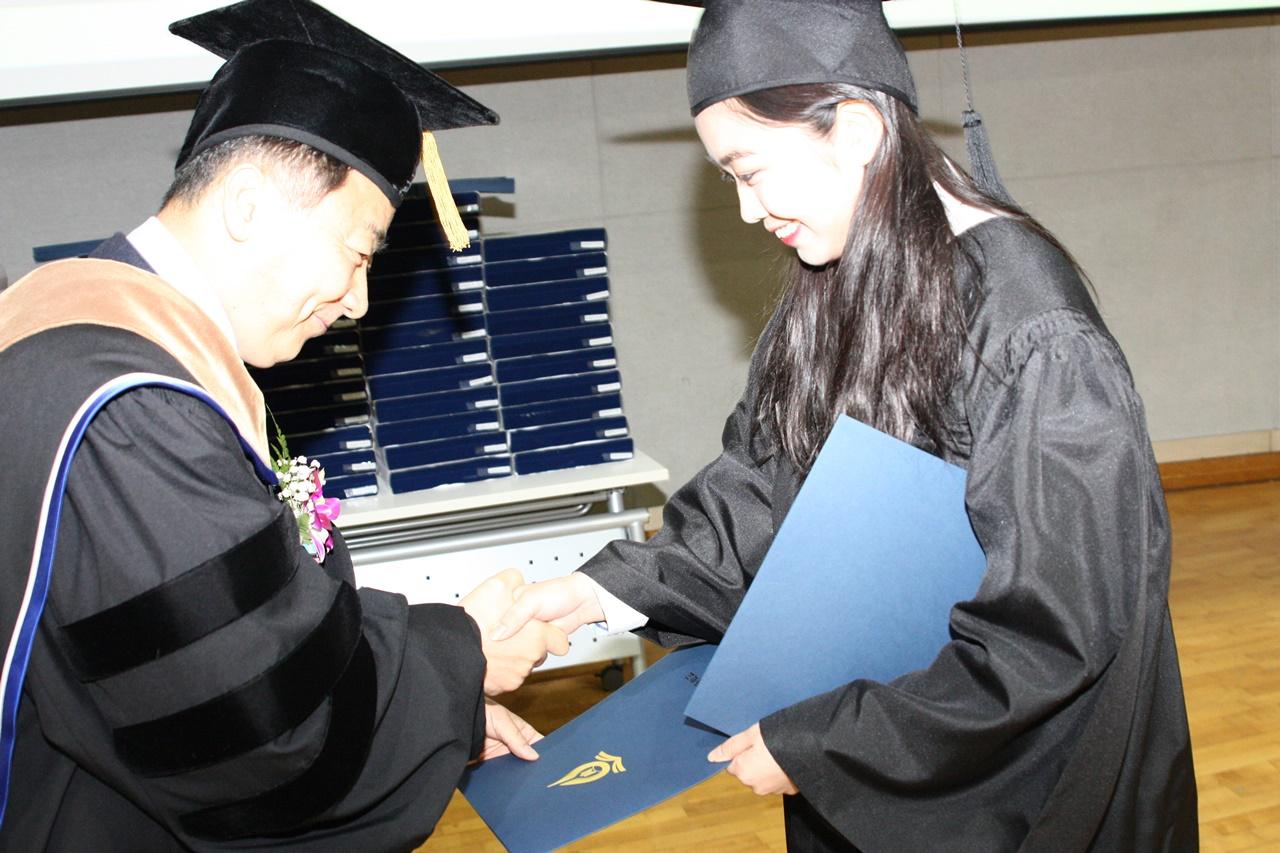 조영만 교장선생님께 졸업장 받는 공정운전과 강연경 학생이 환한 웃음을 보이고 있다