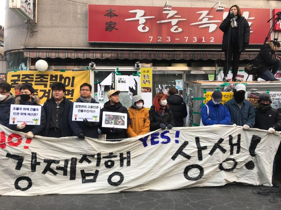 15일 오전 시민과 학생들이 궁중족발 앞에서 기자회견을 열고 집행을 반대하는 구호를 외치고 있다.