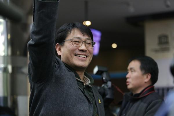 KBS 새노조 성재호 위원장이 고대영 사장 해임 가결 소식을 듣고 기뻐하며 주먹을 쥐고 오른손을 높게 뻗고 있다.