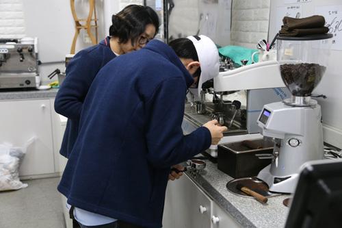 김영실 대표와 발달장애인인 카페 직원이 커피를 내리고 있다.